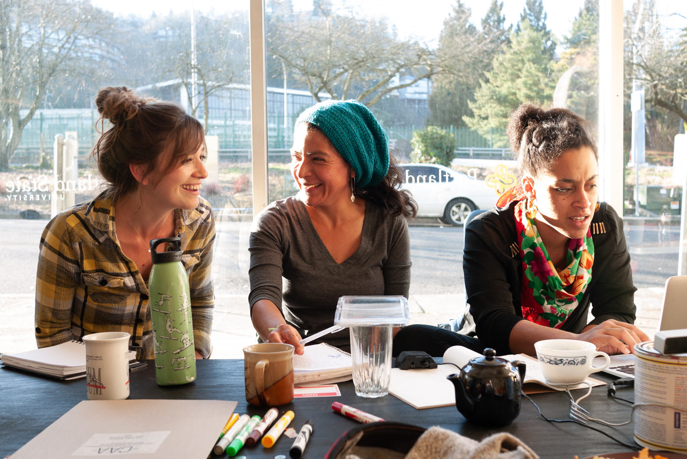 three women at a school for artistic activism workshop