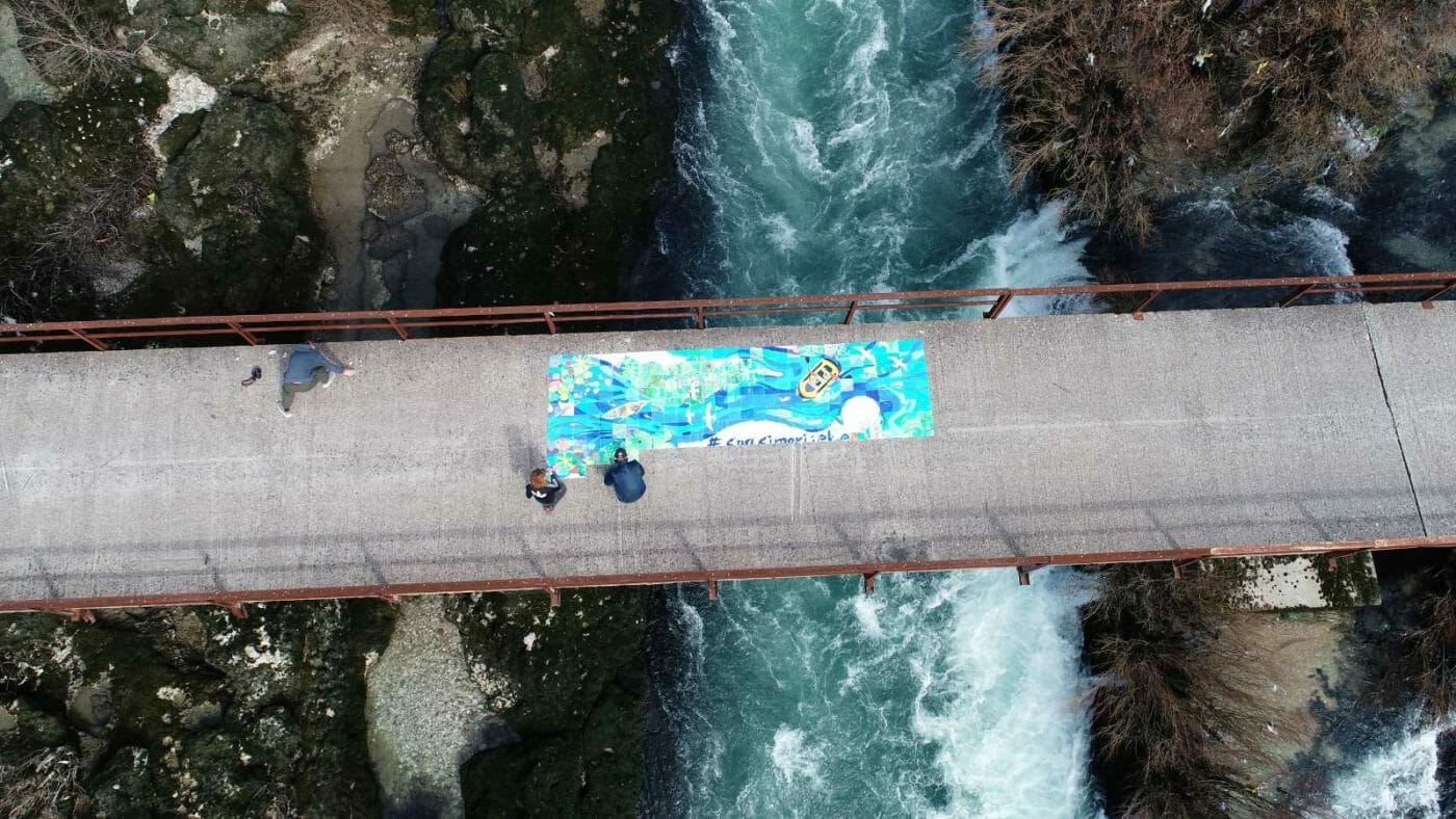 An overhead shot of a collectively created mural is displayed on a bridge over a beautiful rushing river.