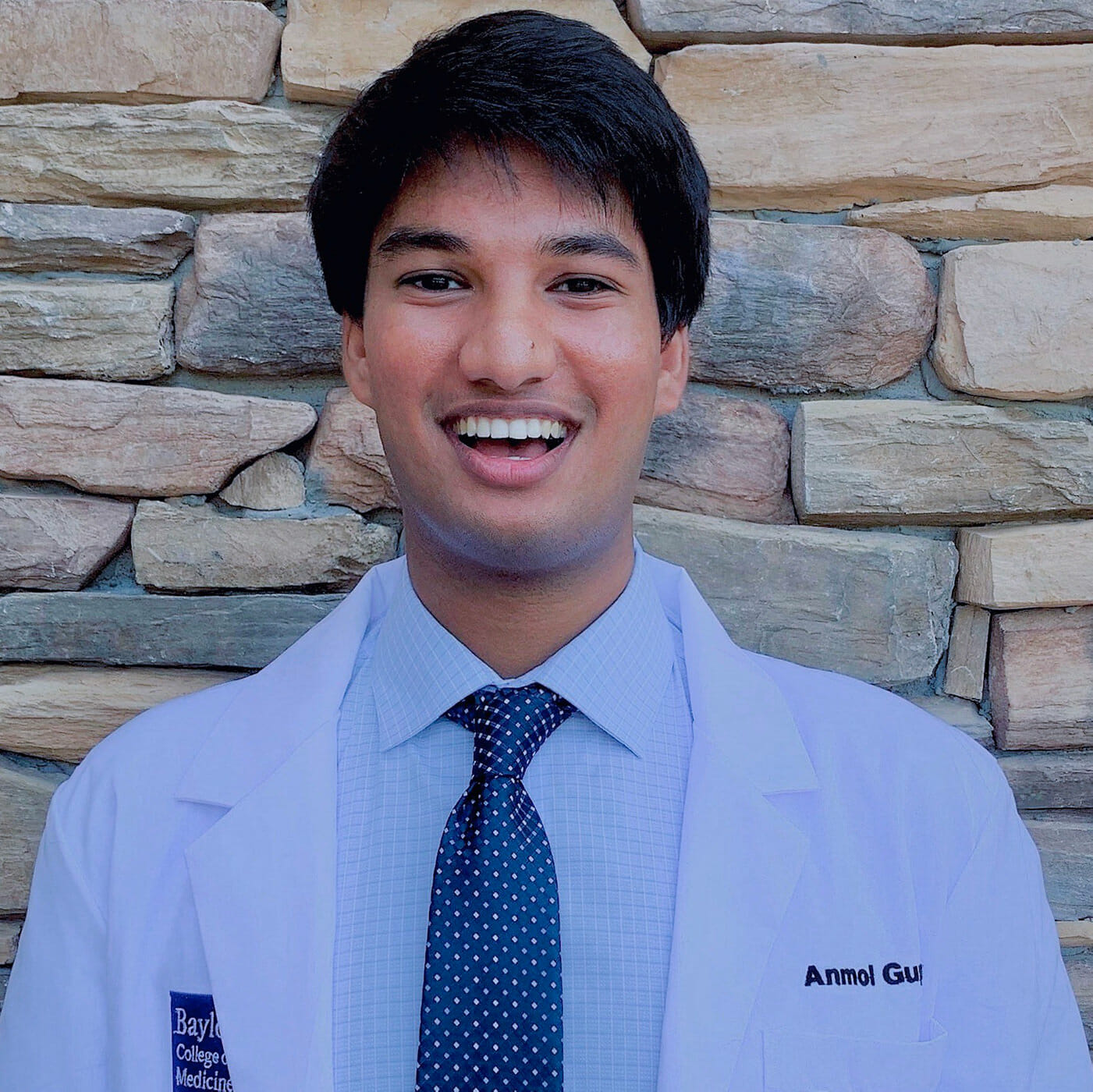 Anmol Gupta in a tie and labcoat
