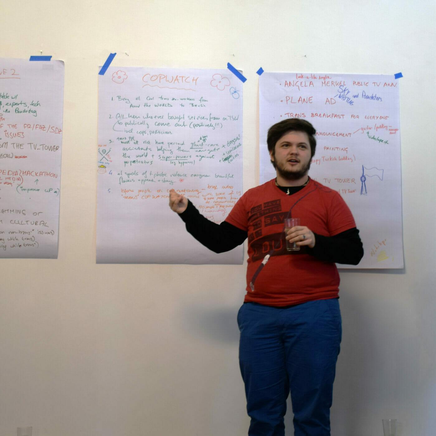 Ari Kajtezovic speaking in front of some whiteboard notes