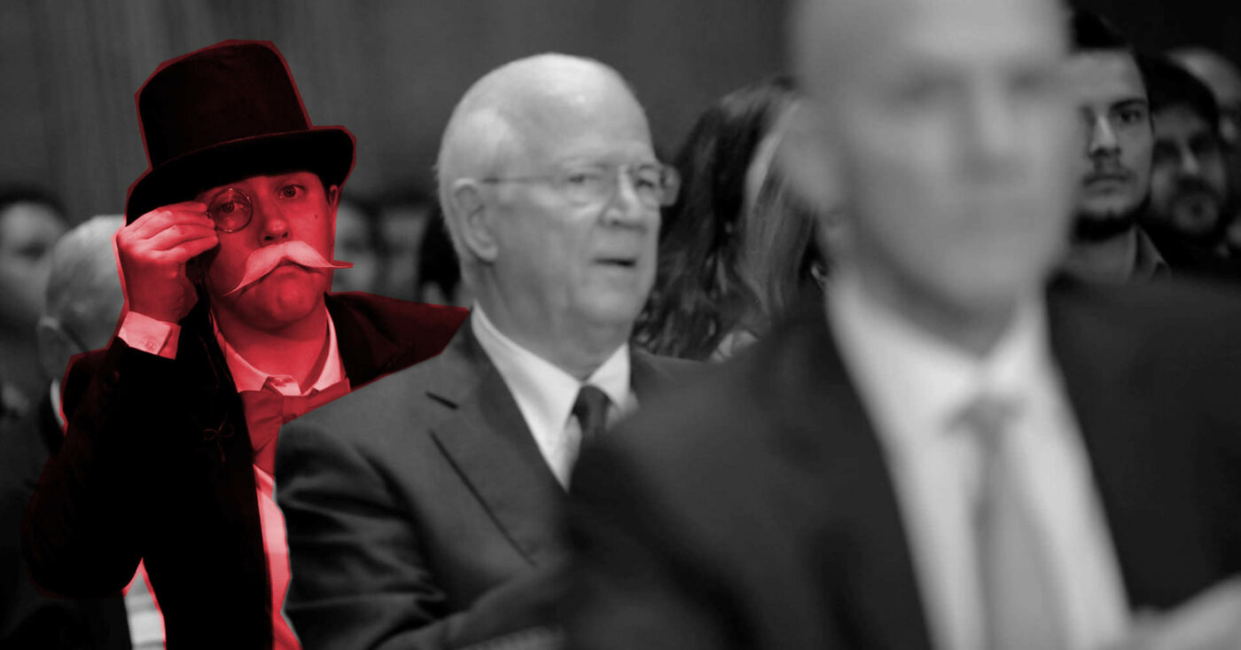 Monopoly Man poses behind an Equifax executive at a government meeting